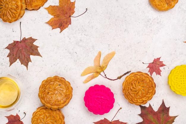 Sfondo autunnale con torte lunari cinesi tradizionali e foglie d'acero autunnali. biglietto di auguri per il festival di metà autunno. copia spazio