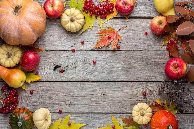 Sfondo autunnale con foglie di acero gialle, mele rosse e zucche. cornice del raccolto autunnale su legno invecchiato.
