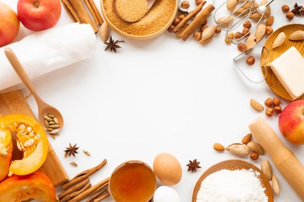 Autunno cottura design del telaio del bordo del fondo con lo spazio della copia per testo. ingredienti da cucina zucca, mele, grano, miele, burro, farina di noci, tonificante, colori arancioni brillanti