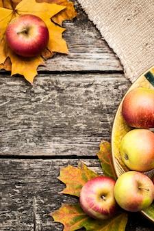 Confine autunnale di mele e foglie di acero sul tavolo di legno. concetto del giorno del ringraziamento