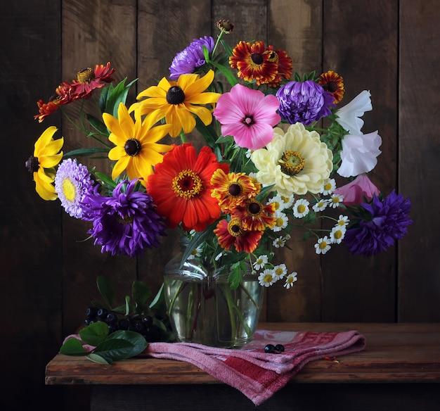 Mazzo autunnale di fiori coltivati in un vaso e un ramo di chokeberry nero sul tavolo.