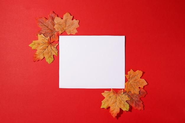 Modello di carta autunnale per la presentazione del design su sfondo rosso con foglie che cadono