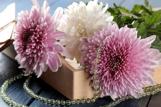 Il crisantemo di autunno fiorisce con le perle e le lettere su una tavola blu scuro