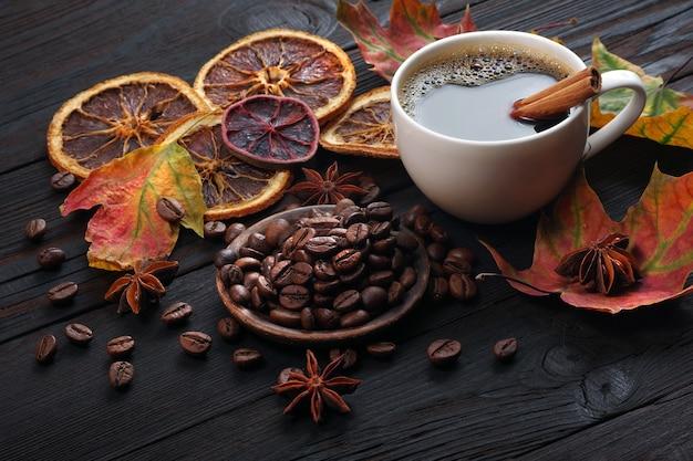 Autunno caffè caffè in una tazza bianca secchi agrumi e spezie su un tavolo di legno secche colorate foglie di acero e una tazza di caffè autunno umore