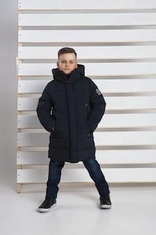 Collezione autunnale di abiti per bambini e ragazzi. giacche e cappotti per il freddo autunnale. i bambini posano su uno sfondo bianco.