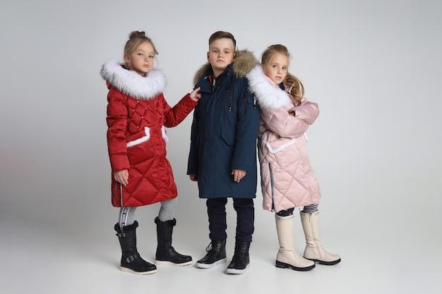 Collezione autunnale di vestiti per bambini e ragazzi. giacche e cappotti per il freddo autunnale. i bambini pongono su uno sfondo bianco
