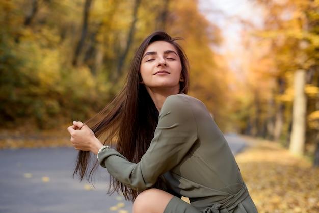 Colori autunnali. bella donna in cappotto in posa nella foresta sul ciglio della strada