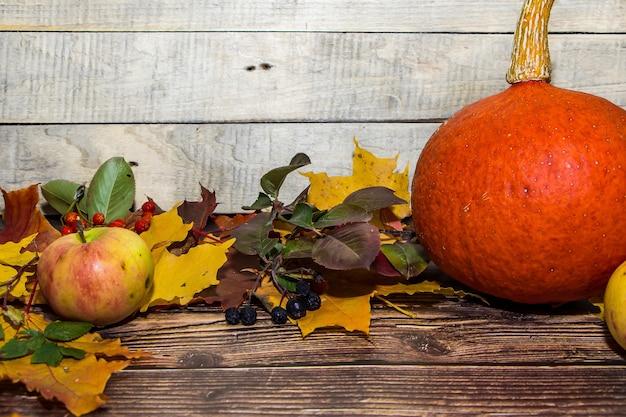 Composizione autunnale di mele, foglie, zucche su uno sfondo di legno marrone scuro.