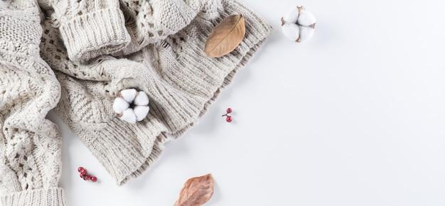 Composizione autunnale fiori di cotone foglie autunnali e maglione da donna su sfondo bianco