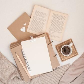 Composizione autunnale tazza di caffè, libro, coperta, taccuino, maglione moda donna.