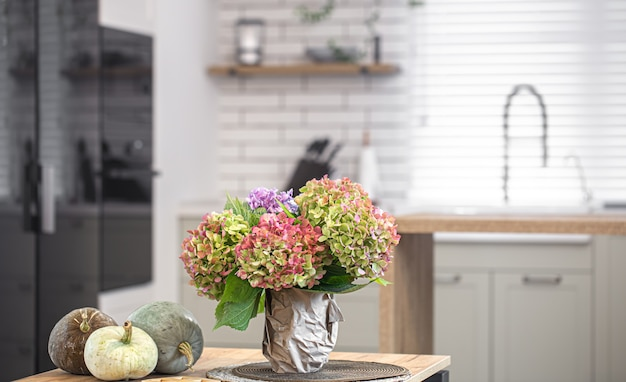 Composizione autunnale di fiori di ortensie e zucche all'interno di una moderna cucina.