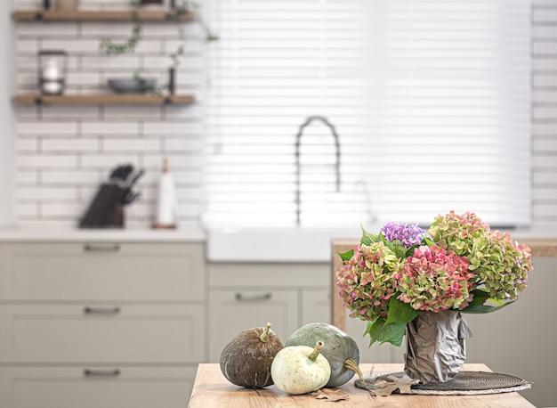 Composizione autunnale di fiori di ortensie e zucche sullo spazio degli interni di una cucina moderna.
