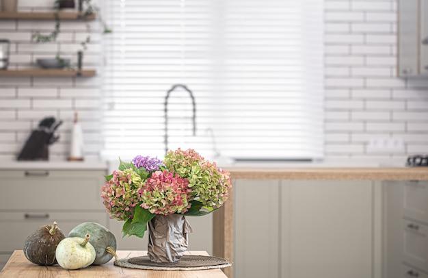 Composizione autunnale di fiori di ortensie e zucche sulla parete dell'interno di una cucina moderna.