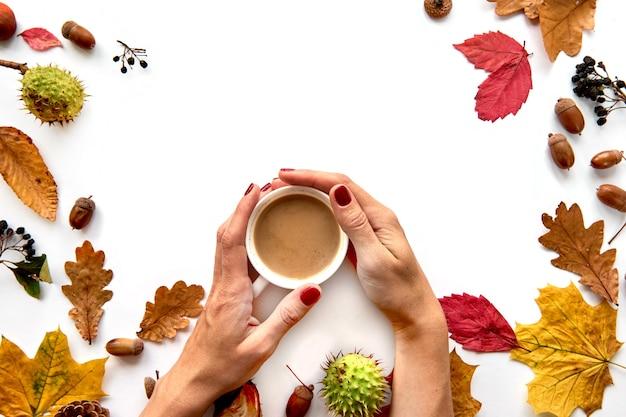 Composizione autunnale. cornice fatta di foglie secche, rami, pigne, bacche, ghiande e mano con una tazza di caffè su sfondo bianco. modello mockup autunno, halloween. lay piatto, copia dello sfondo dello spazio.