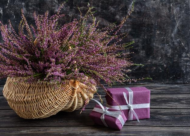 Composizione autunnale di erica in un cesto di vimini e regali ancora in vita