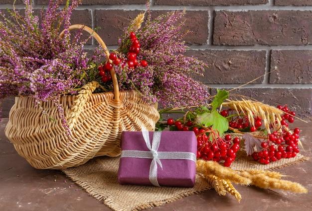 Composizione autunnale di erica in un cesto di vimini spighe di grano viburno e doni natura morta
