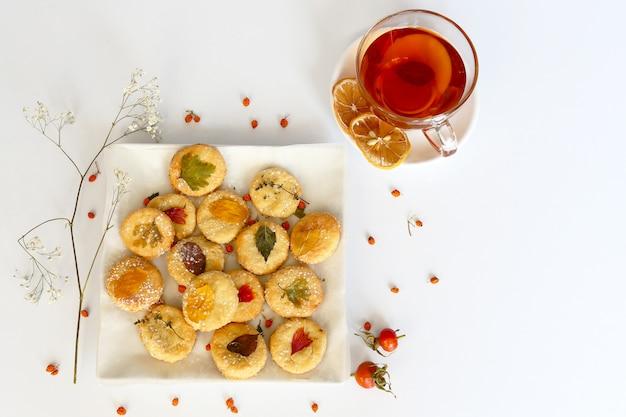 Composizione autunnale, biscotti fatti in casa con tè e foglie d'autunno