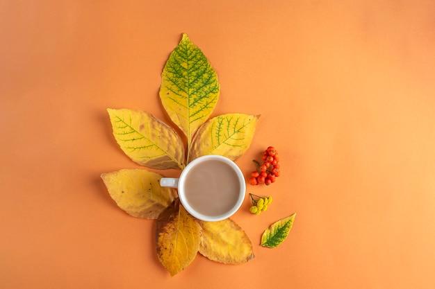 Composizione autunnale, layout di foglie secche gialle e tazza di caffè su sfondo arancione. natura morta autunnale minimalista, elegante e creativa. lay piatto, copia spazio.