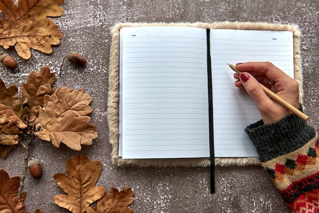 Composizione autunnale fatta di foglie secche marroni e ghiande su fondo di cemento scuro. taccuino in bianco del modello del modello e mano con una penna. autunno, halloween. lay piatto, copia dello sfondo dello spazio.