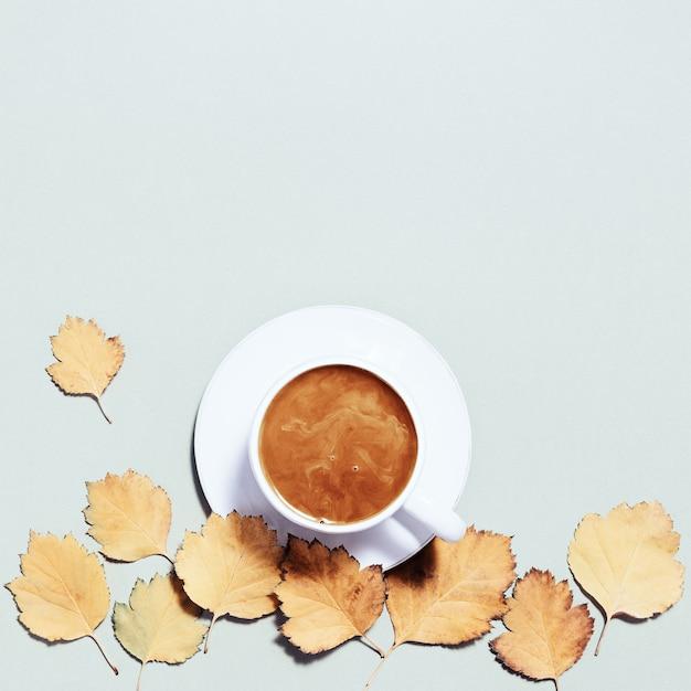 Composizione autunnale con tazza di caffè e foglie autunnali atmosfera accogliente e caffè caldo con latte