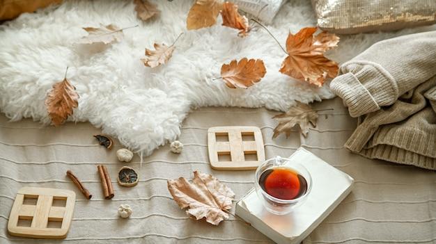 Composizione autunnale con una tazza di tè, un libro e dettagli di decorazioni autunnali.