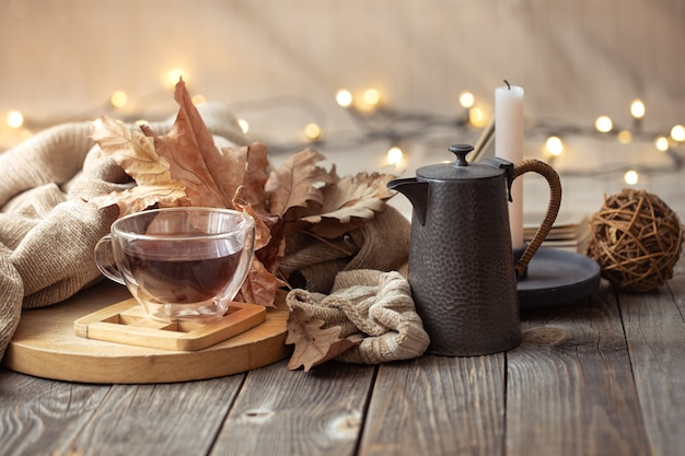 Composizione autunnale con una tazza di tè e oggetti decorativi. concetto di comfort domestico della stagione fredda.