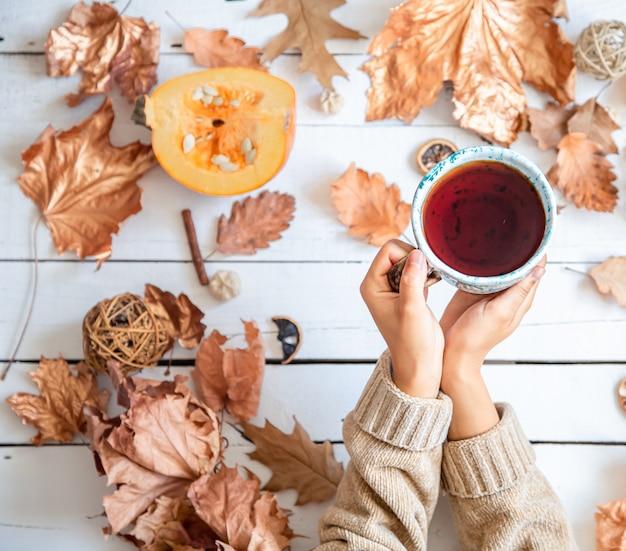 Composizione autunnale con foglie secche e mani femminili che tengono una tazza di tè piatto laici.