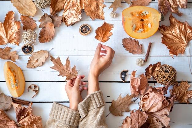 Composizione autunnale con foglie secche, mani femminili e zucca sul tavolo in legno bianco laici piatta.