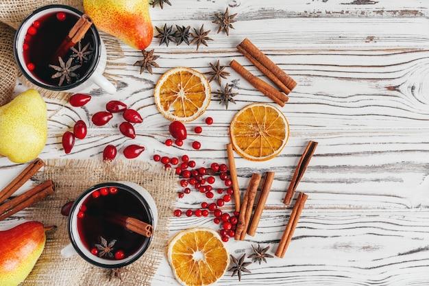 Composizione autunnale con vin brulè caldo e spezie su fondo in legno