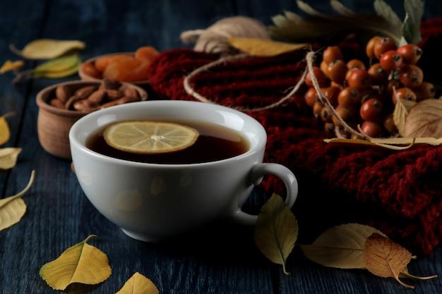 Composizione autunnale con bacche di noci di tè calde e foglie gialle autunnali su un tavolo di legno blu scuro