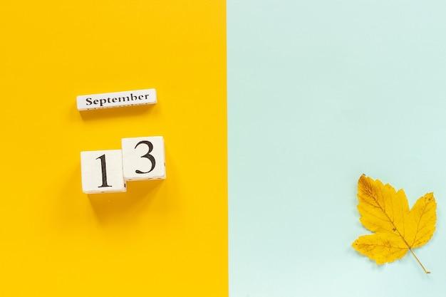Composizione autunnale calendario in legno 13 settembre e foglie autunnali gialle su sfondo blu giallo
