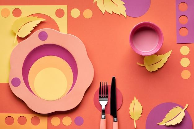 Concetto di autunno piatto giaceva in colori audaci con piastra, forchetta, coltello e foglie di autunno decorative