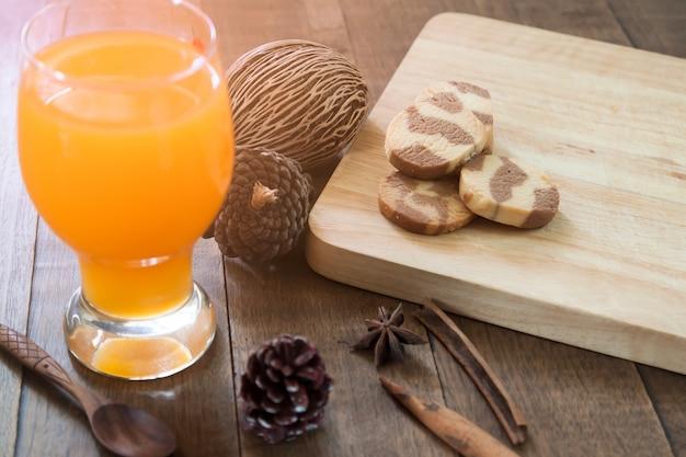 Concetto di autunno con succo d'arancia e biscotti sul tavolo di legno