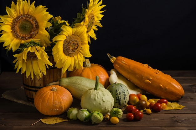Cornucopia d'autunno. natura morta con girasoli di verdure su una superficie nera con spazio di copia. ringraziamento e raccolto.