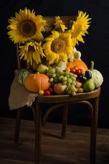 Cornucopia d'autunno. natura morta con girasoli di frutta e verdura su una superficie nera. ringraziamento e raccolto.