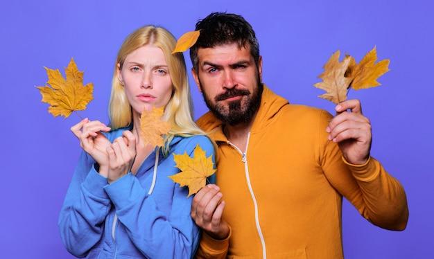 Autunno coppia con foglie di acero. abbigliamento autunnale. uomo e donna in abiti casual. pubblicità del negozio di abbigliamento.