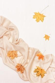 Composizione accogliente autunnale con foglie secche di acero e sciarpa beige pastello su legno bianco white