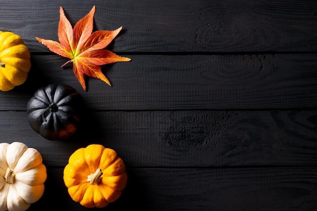 Decorazioni autunnali da foglie di acero e zucche sul tavolo di legno nero. copia spazio.