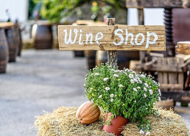 Decorazione di autunno con fieno, fiori e zucche in un negozio di vino, segno