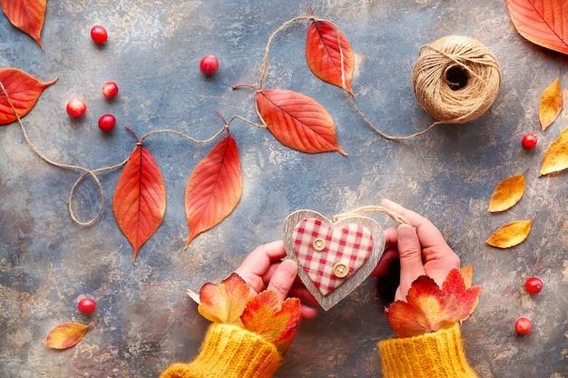 Decorazioni autunnali con materiali naturali, foglie vibranti. le mani in maglione arancione tengono il cuore di legno. caduta stagionale laici piatta.