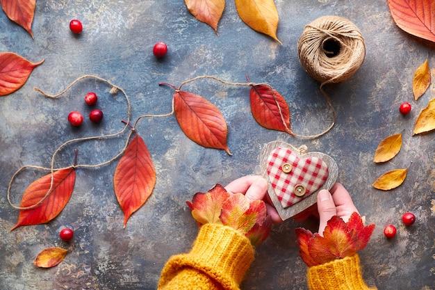 Decorazioni autunnali realizzate con materiali naturali, foglie autunnali luminose. le mani in maglione arancione tengono il cuore di legno. caduta stagionale laici piatta.