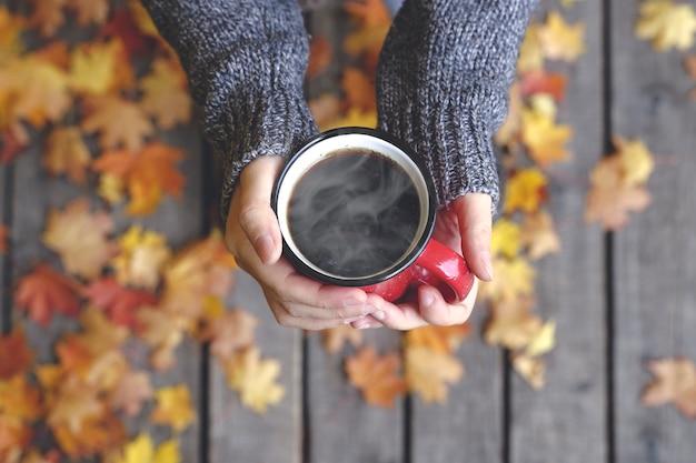 Bere tè o caffè autunnale in mano sullo sfondo di foglie gialle di ottobre comfort autunnale e mo...