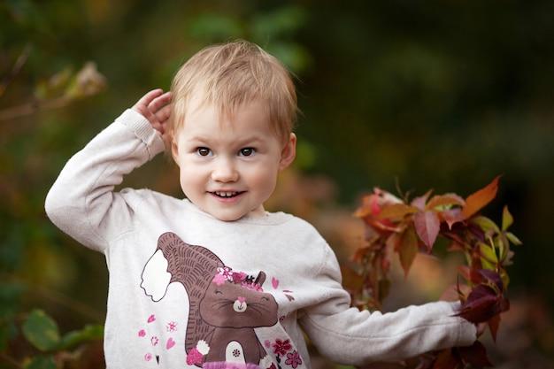 Ritratto emotivo autunnale di una bambina bambina graziosa con foglie di uva rossa nel parco autunnale au