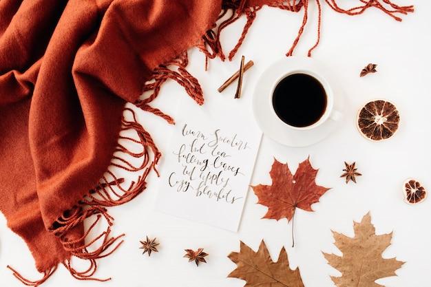 Calligrafia di composizione autunnale con tazza di caffè, coperta di zenzero, foglie secche, stella di cinnamons, anice e arancia sul tavolo bianco