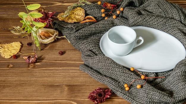Autunno, foglie secche e fiori autunnali, pullover caldo e tazza bianca vuota per caffè o tè sul legno
