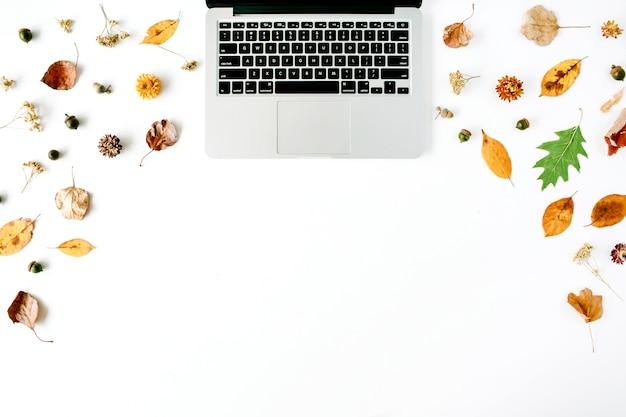 Autumn fall flat lay, top view home office desk. area di lavoro con laptop, ghianda, foglie gialle su bianco