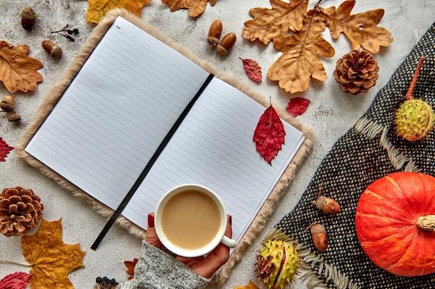 Composizione autunnale, autunnale o di halloween fatta di foglie secche, zucca, pigne, ghiande, sciarpa calda e mano con una tazza di caffè su fondo di cemento. taccuino in bianco del modello del modello con lo spazio della copia.