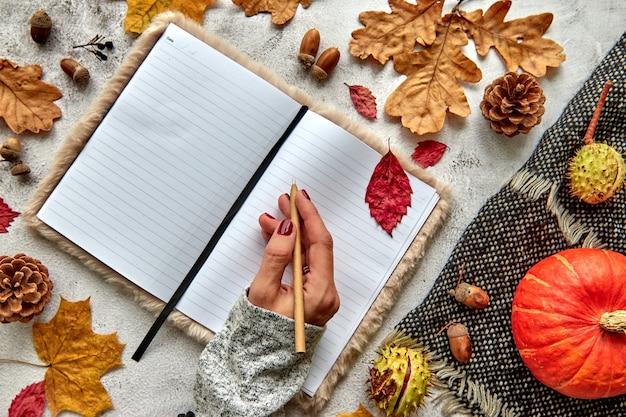 Composizione autunnale, autunnale o di halloween fatta di foglie secche, zucca, pigne, ghiande, sciarpa calda e mano con una penna su fondo di cemento. taccuino in bianco del modello del modello con lo spazio della copia.