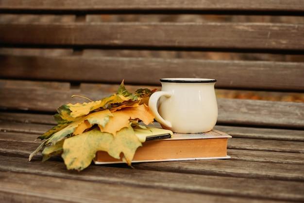 Autunno autunno umore sfondo foglie autunnali libro e tazza di cacao su panca di legno umore autunnale