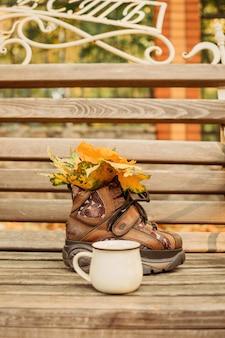 Autunno autunno sfondo umore foglie autunnali uno stivale e una tazza di cacao su una panca di legno umore autunnale